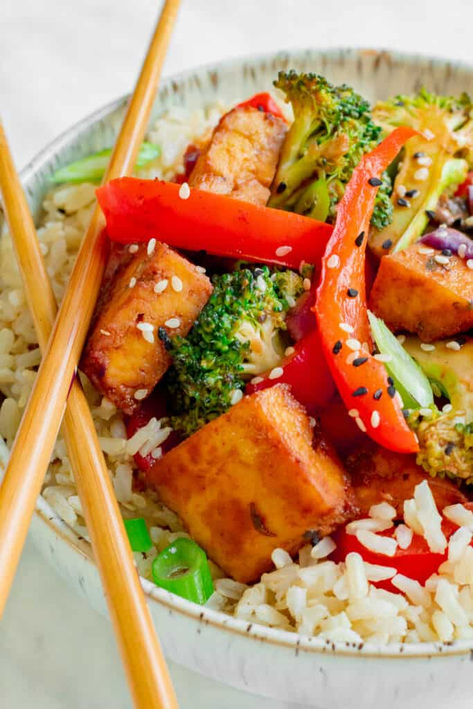 Close up of Crispy Tofu Hoisin Stir-fry in bowl with chopsticks. Vegan, GF & Healthy! Georgie Eats.
