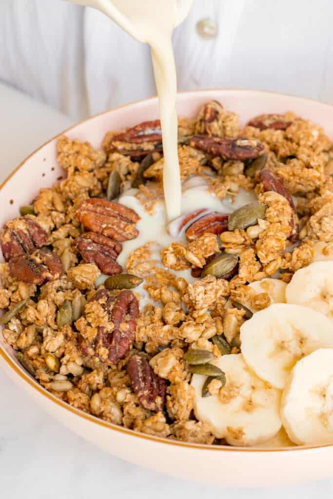 Pouring milk into a bowl of maple pecan sea salt granola. Vegan, GF & healthy.