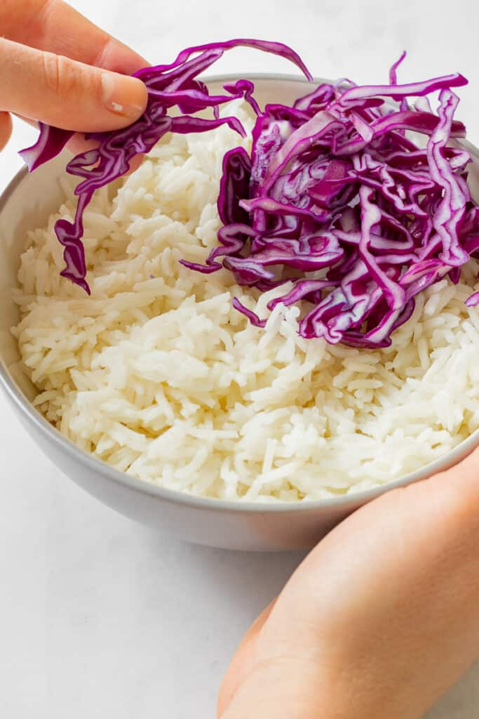 Rice being topped with red cabbage.