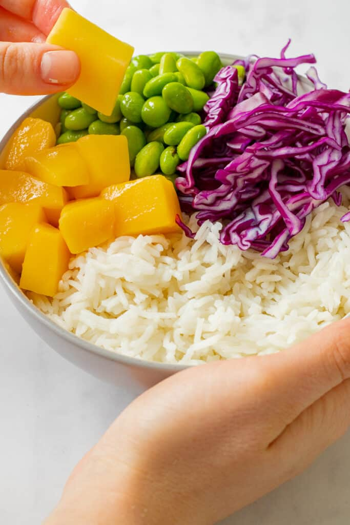 Rice, red cabbage, edamame beans and mango in a bowl.