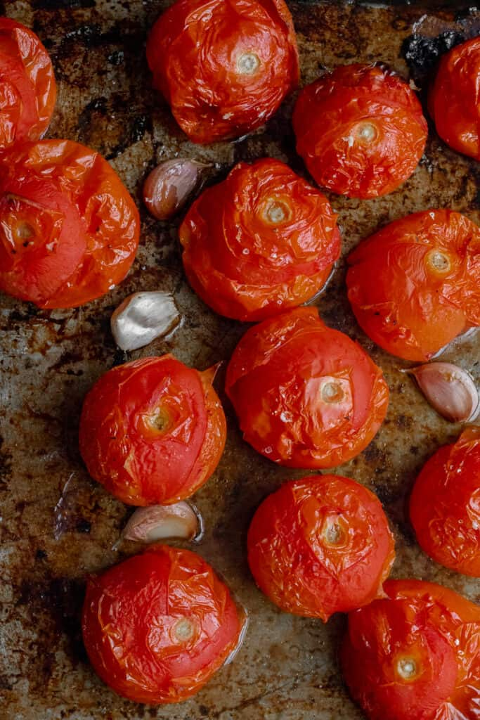 Roasted tomatoes on a baking tray.