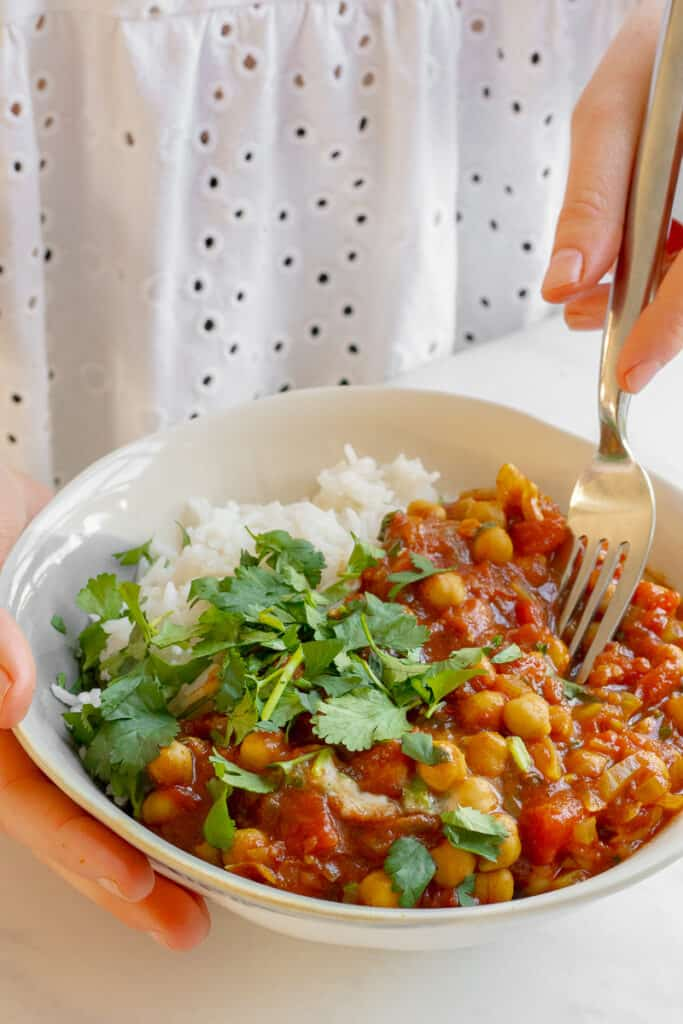 Holding a bowl of Quick Chickpea Curry - Vegan, GF & Healthy! Georgie Eats.