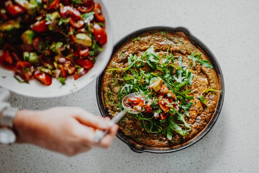 Spooning the avocado salsa on top of the Mexican Frittata