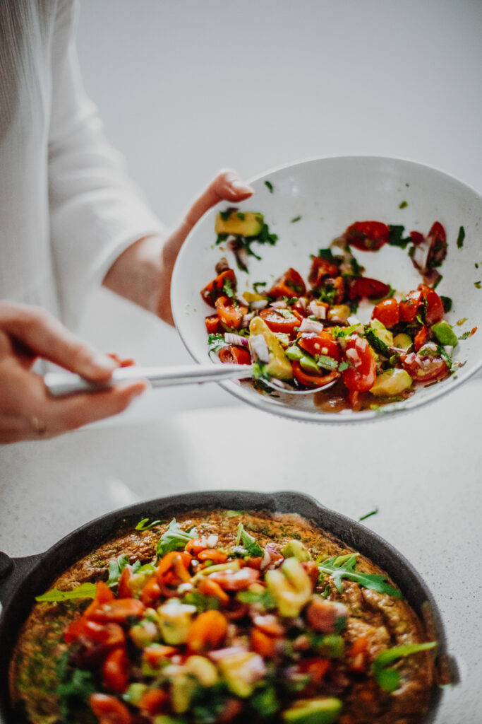 Spooning the Avocado Salsa onto the Mexican Frittata - GF & Healthy! Georgie Eats.