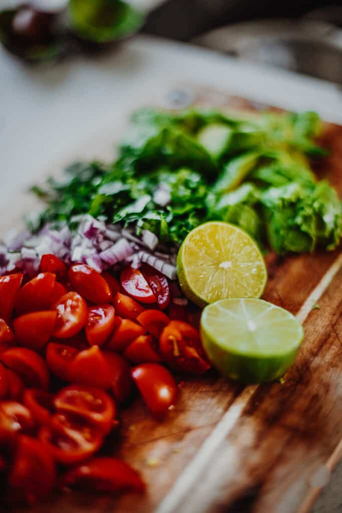 A chopping board filled with chopped tomatoes, red onion, coriander, avocado and lime