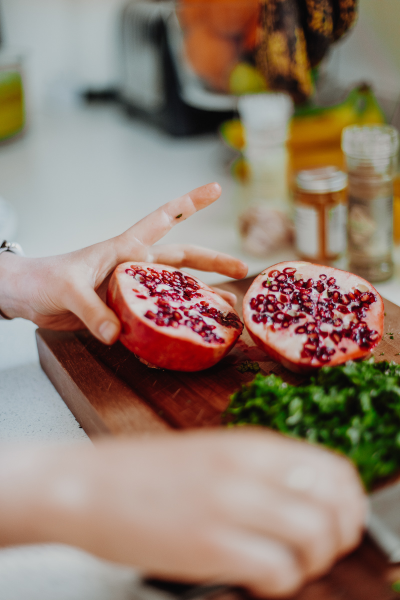 A chopping board with chopped herbs and fresh pomegranate.