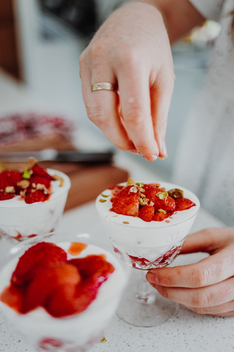 sprinkling pistachios over Strawberry & Elderflower Fools - Vegan, GF & Healthy! Georgie Eats.