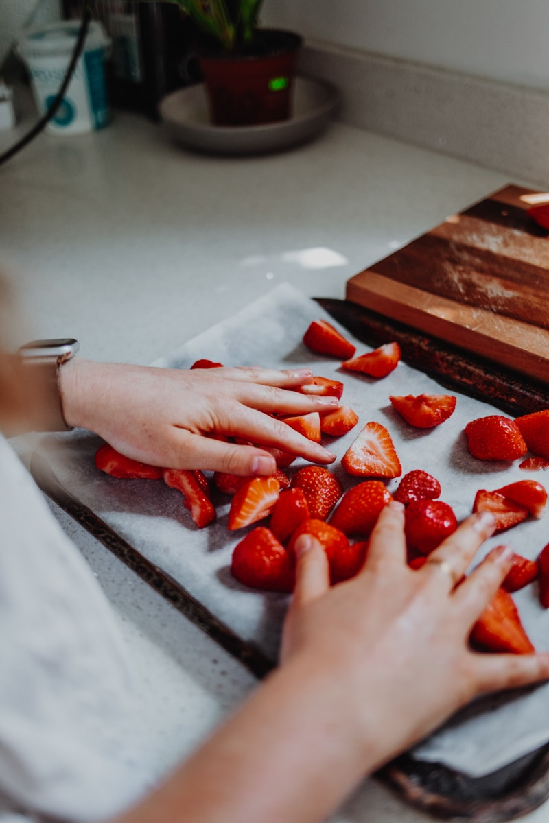 laying the strawberries out onto a baking tray