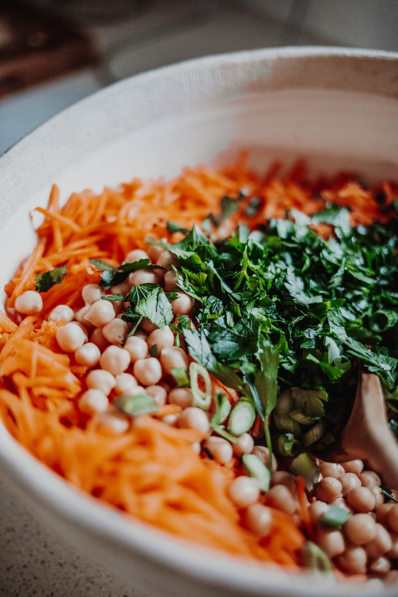Combining all the ingredients for carrot & chickpea salad.
