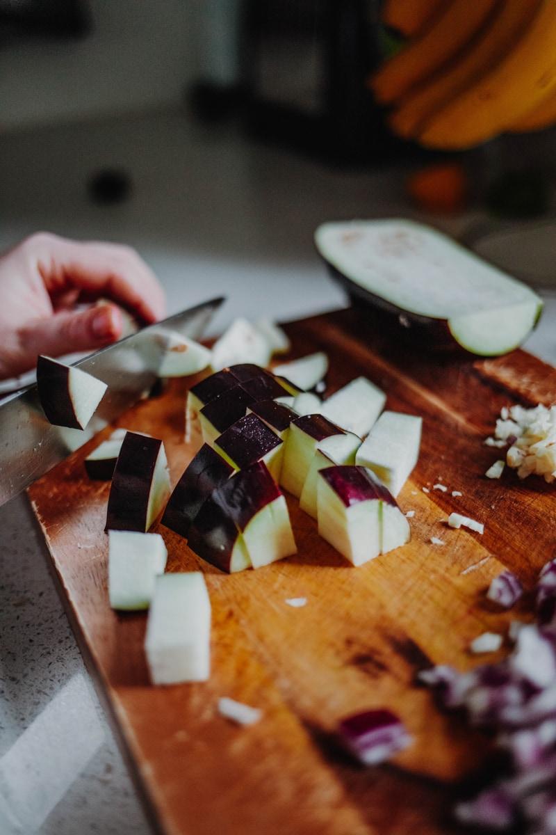 chopping an aubergine into chunks