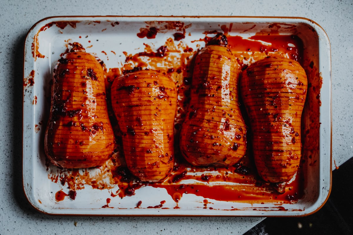 four hasslebacked squash on a baking tray