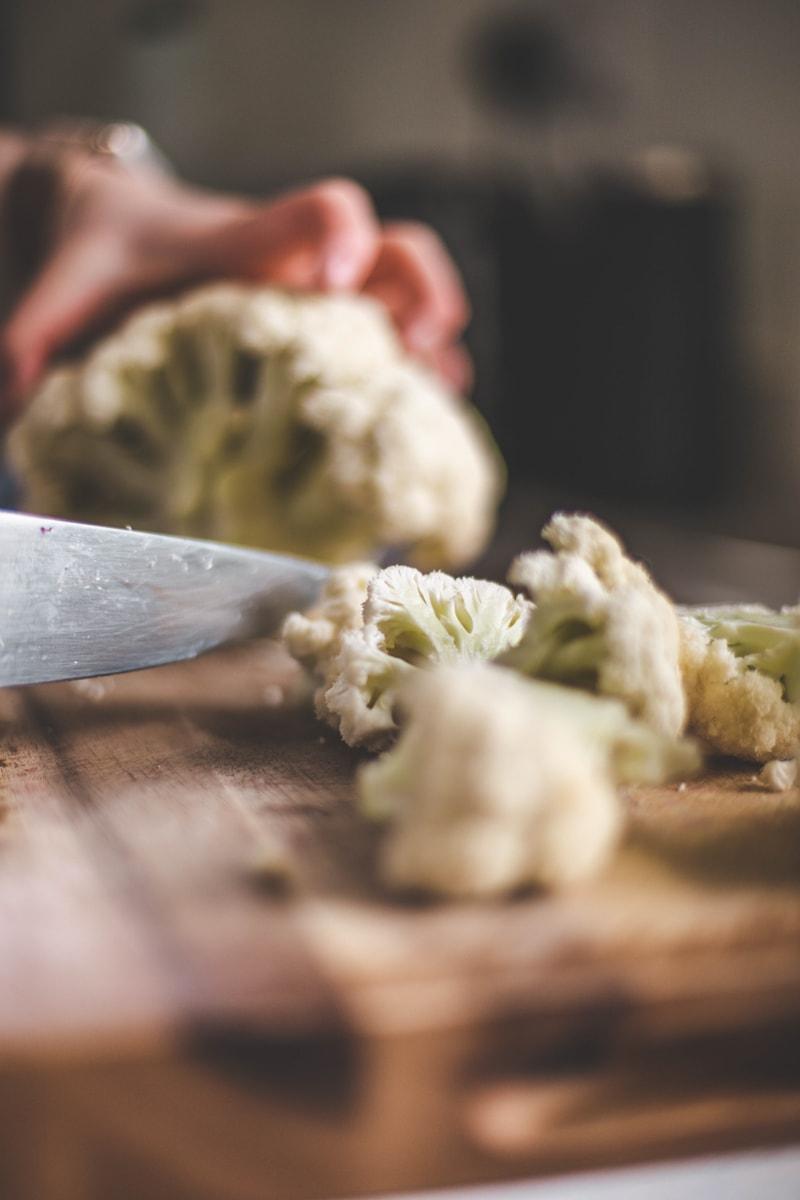chopping cauliflower on a board