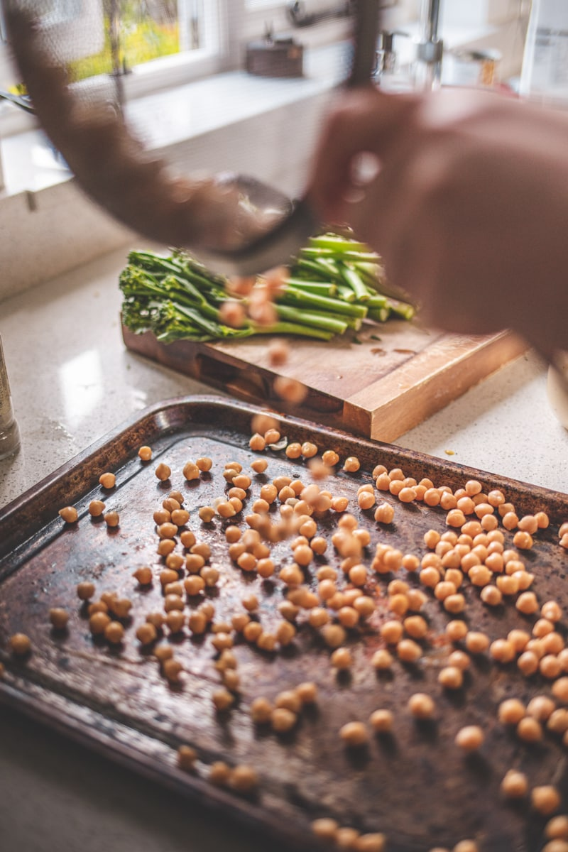 pouring chickpeas onto a baking tray